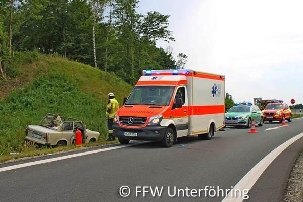 Unfallfahrzeug im Straßengaben und Rettungswagen
